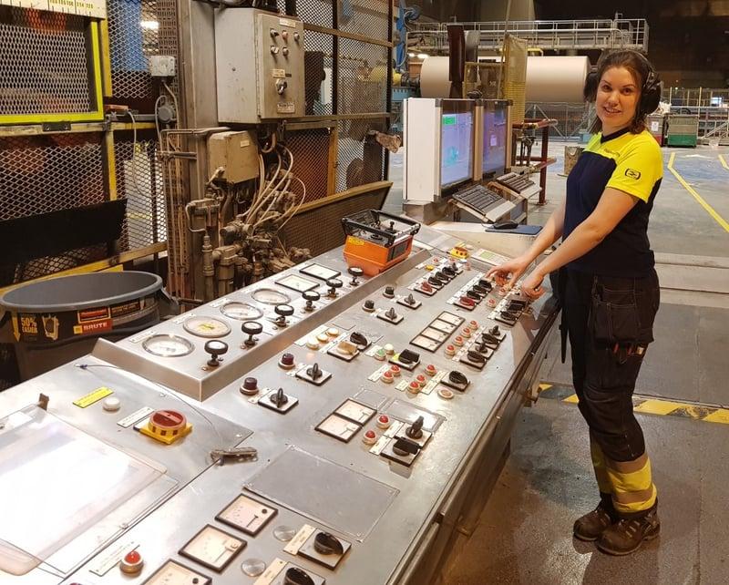 En kvinna i arbetskläder står framför en instrumentpanel i en industrilokal.